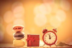 Uhr und französische macarons mit Geschenk Lizenzfreies Stockbild