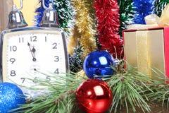 Uhr und Geschenkbox auf einem Weihnachtshintergrund Stockfotos
