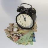 Uhr und kanadisches Geld Stockbilder