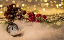 Uhr und Kegel des neuen Jahres der Weinlese bedeckt mit Schnee stockfotografie