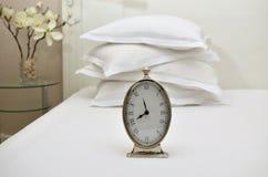 Uhr und Kissen auf einem Bett Lizenzfreie Stockbilder