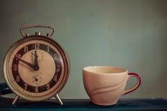 Uhr und Schale auf Weinlesehintergrund Stockbild
