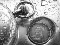 Uhr-und Silbermünze stockbilder