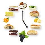 Uhr vereinbarte von den Kuchen und von Früchten, die auf Weiß lokalisiert wurden lizenzfreie stockbilder