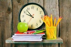 Uhren, ein Apfel und Schulzubehör Lizenzfreie Stockbilder