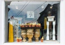 Uhren in einem Fenster - Reflexionen und Anzeige von antiken Uhren und von Baby duckt sich in Blumentöpfe in Cape Cod-Fenster mit lizenzfreie stockfotografie