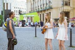 Uhren eines singen obdachlose Mannes als zwei Mädchenzwillinge und spielen Gitarre Lizenzfreie Stockfotografie