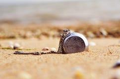 Uhren und Muscheln auf dem Sand stockbild