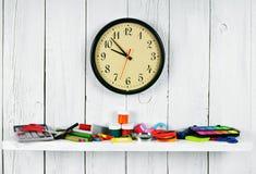 Uhren und Schulwerkzeuge auf einem hölzernen Regal Lizenzfreies Stockbild