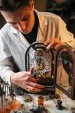 Uhrmacher, der alte Tischuhr hält Lizenzfreies Stockbild