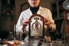 Uhrmacher, der alte Tischuhr hält Stockfotografie