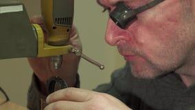 Uhrmacher macht Perforierung in irgendeinem Uhrstück stock video footage