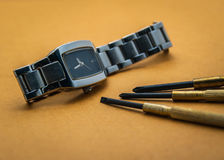 Uhrreparaturwerkzeuge mit braunem Hintergrund stockbild