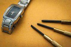 Uhrreparaturwerkzeuge mit braunem Hintergrund Lizenzfreies Stockfoto
