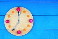 Uhrskala hergestellt vom Rettich und von der Karotte Lizenzfreie Stockbilder