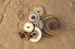 Uhrwerkmechanismus auf dem Sand Stockfotos