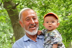 UHUM,乌兹别克斯坦- 2011年5月16日:一个老乌兹别克人人的画象有他的孙子的在Uhum村庄 图库摄影