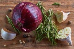 Ui, knoflook, rozemarijn en peper op houten raad Royalty-vrije Stock Afbeelding
