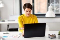Uiontwerper met laptop die op kantoor werken royalty-vrije stock afbeeldingen