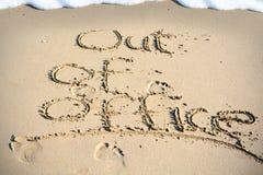 Uit bureautekst in zand op een strand wordt geschreven dat stock foto's