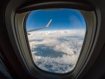 Uit het venster van luchtvliegtuig en vleugel in de blauwe hemel Royalty-vrije Stock Foto's