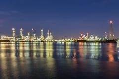 Uit nadruk, Olieraffinaderij bij schemering met rivierbezinning Stock Afbeeldingen