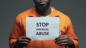 Uitdrukking van het einde de fysieke misbruik op karton in handen van zwarte gevangene, aanval stock videobeelden