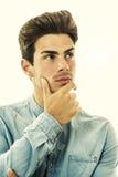 Uitdrukking van twijfel of keus Jonge mens het denken Op wit Royalty-vrije Stock Foto's