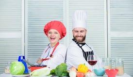 Uiteindelijke het koken uitdaging Familie het koken in keuken man en vrouwenchef-kok het koken vegetari?r Eenvormige kok Het op d royalty-vrije stock foto