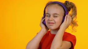 Uiterst blij kind die aan muziek in hoofdtelefoons luisteren, die van favoriet lied genieten stock videobeelden