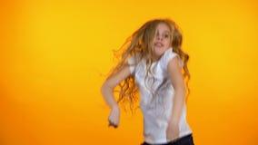 Uiterst blij tienermeisje die op oranje achtergrond, het vieren voltooiing dansen stock videobeelden