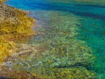 Uiterst duidelijk ondiep water op klein rotsachtig strand in Kreta, Griekenland stock foto's