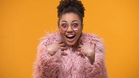Uiterst gelukkige die vrouw bij modetrends, millennials, gele achtergrond wordt verbaasd stock video