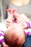 Uiterst kleine baby die met zijn hoofd naar de camera liggen Stock Foto