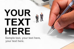 Uiterst kleine businessdolls bij document en hand het ondertekenen Stock Fotografie