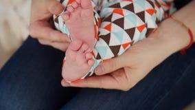 Uiterst kleine leuke pasgeboren babyvoet in vrouwelijke handen stock footage