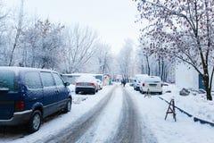 Uiterst kleine stadsweg na nachtsneeuwval Lijn van geparkeerde auto's royalty-vrije stock foto