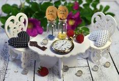 Uiterst kleine uitstekende voorwerpen - flessen, klok, sleutel - op kleine lijst met witte erachter stoelen en wilde rozen Stock Afbeeldingen