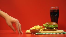 Uiterst kleine vrouwelijke vingers die aan frieten lopen, die één nemen, door snel voedsel worden verleid stock footage