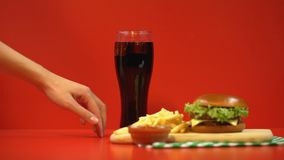 Uiterst kleine vrouwenvingers die aan frisdrank lopen, die glas nemen, door snel voedsel wordt verleid stock videobeelden