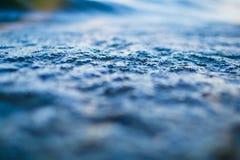 Uiterst kleine waterbellen op oppervlakte van blauwe golfmacro royalty-vrije stock foto's