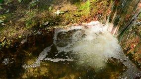Uiterst kleine waterval in kleine rivier met snel stromend duidelijk water stock footage