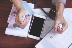 Uiterste termijnkalender, slimme telefoon, geld, creditcard, calculator en besparingsrekening op lijst met onduidelijk beeldachte stock fotografie
