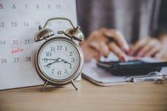 Uiterste termijnkalender voor belastingenbetaling met wekker bij bureau en onduidelijk beeld het bedrijfsvrouw berekenen stock fotografie