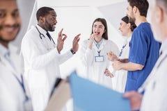 Uitgaande artsen die tijdens pauze in het ziekenhuis vertellen stock fotografie
