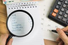 Uitgave en begrotingsconcept, het vergrootglas van de handholding over lijst van uitgave in kleine blocnote en calculator op Desk royalty-vrije stock afbeelding