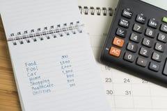 Uitgave en begrotingsconcept, lijst van uitgave in kleine blocnote en calculator op Desktopkalender op houten lijst stock foto