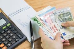 Uitgave en begrotingsconcept, vrouwenhand die Euro bankbiljetgeld met lijst van uitgave in kleine blocnote en calculator op houte stock afbeeldingen