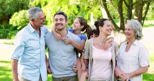 Uitgebreide familie die bij de camera in de tuin lachen stock videobeelden
