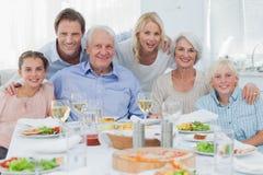 Uitgebreide familie die bij dinerfamilie glimlachen stock afbeeldingen